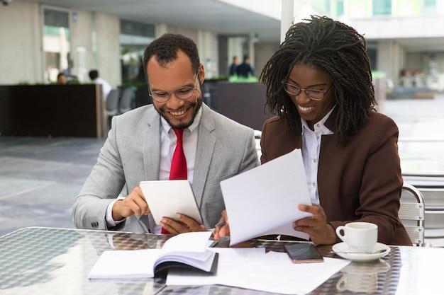 ドキュメントをチェックする陽気なビジネス同僚 無料写真