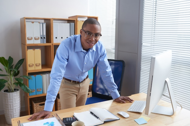 Cheerful business executive leaning on his boss table Free Photo