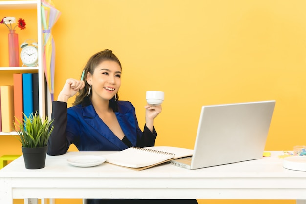 Cheerful business lady working on laptop in office Free Photo