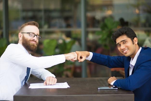 Cheerful business partners making fist bump Free Photo