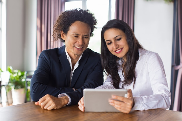 Cheerful business people discussing data on tablet Premium Photo