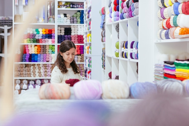 Cheerful business woman organizing wool yarns at her own retail shop Premium Photo