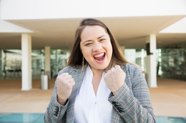 Cheerful business woman pumping fists outdoors Free Photo