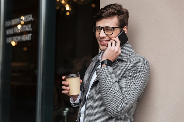 Cheerful businessman in eyeglasses and coat talking by smartphone Free Photo