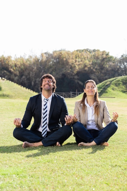 Cheerful businesspeople in the lotus position Free Photo