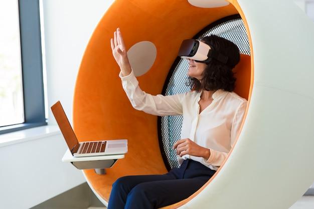 Cheerful businesswoman with laptop watching virtual presentation Free Photo