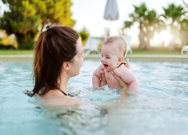 スイミングプールで泳ぐ方法を学ぶ陽気な白人6ヶ月の男の子。彼女の息子を持つお母さん。プールのコンセプトで初めて。 Premium写真