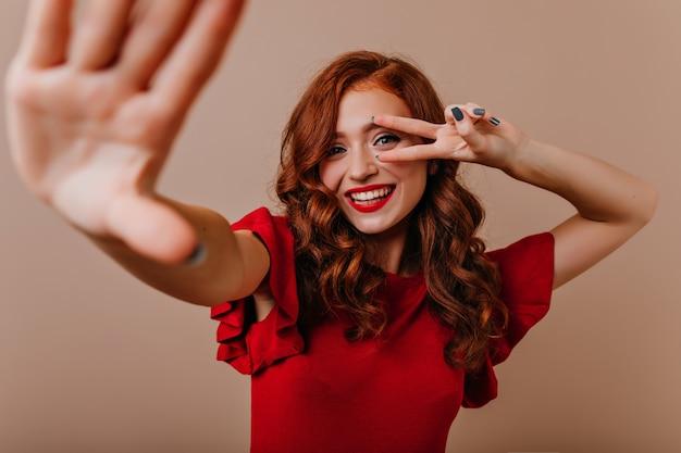 Allegra ragazza caucasica in abito rosso ballando. meravigliosa giovane donna con i capelli allo zenzero in posa con il segno di pace. Foto Gratuite