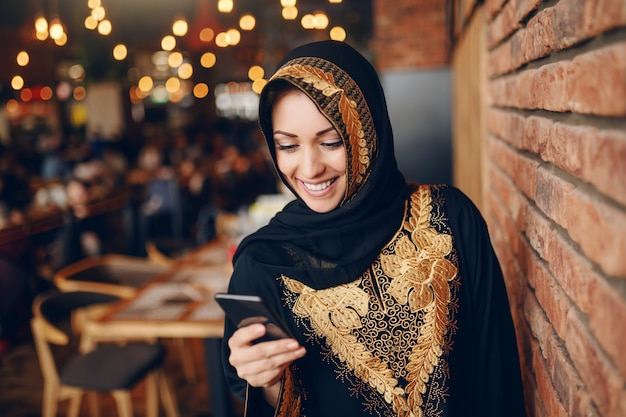 Cheerful charming muslim woman in abaya using smart phone for reading or writing message while sitting in cafeteria. Premium Photo