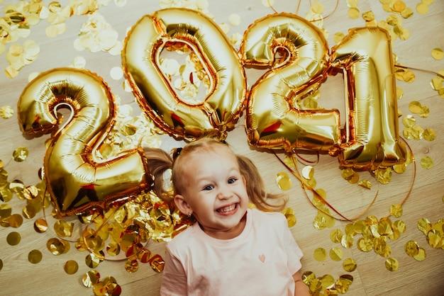 숫자 2021을 가진 쾌활한 아이 소녀는 위에서 비행하는 황금색 색종이에 기뻐합니다. 프리미엄 사진