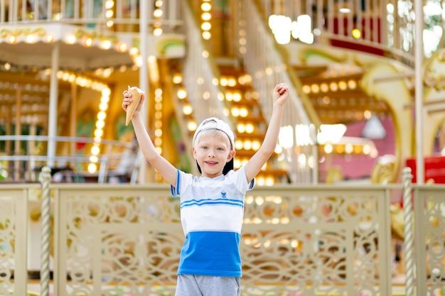 Веселый ребенок гуляет в парке развлечений Premium Фотографии