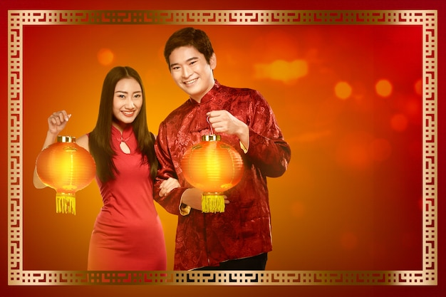 Cheerful chinese couple in traditional dress holding red lanterns Premium Photo