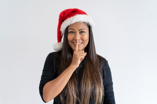 Cheerful christmas lady showing shh gesture Free Photo