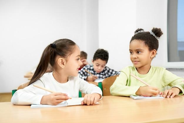 学校の教室でテーブルに座っている陽気な同級生 Premium写真