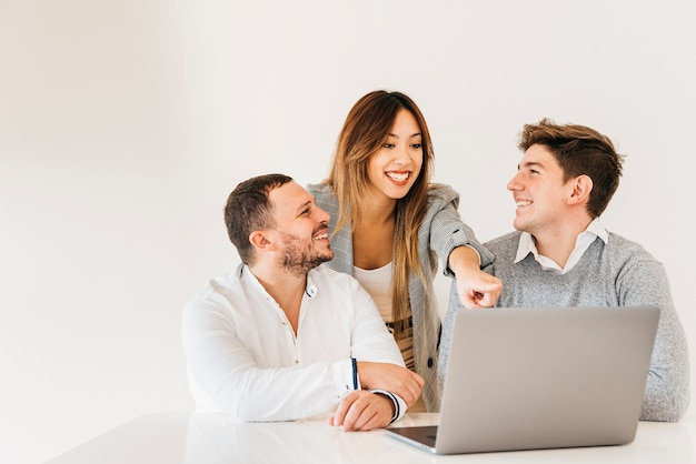 Cheerful colleagues looking at project on laptop in office Free Photo