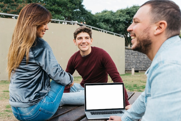Cheerful colleagues working on laptop outside Free Photo