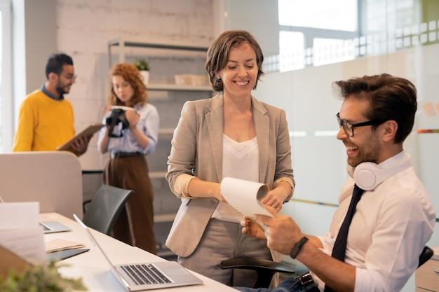 オフィス、コピースペースで一緒に販売を分析しながら書類を閲覧するブローカーの明るく自信のあるチーム Premium写真
