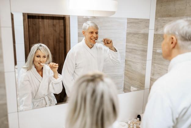陽気なカップルがバスルームの鏡で歯を磨きます。朝は自宅でバスローブを着た白髪の成熟した男女 Premium写真