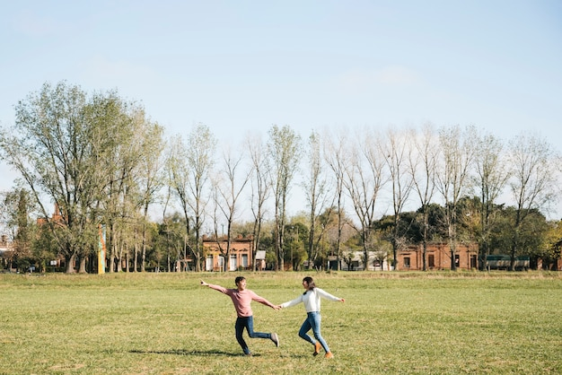 Cheerful couple running across field holding hands Free Photo