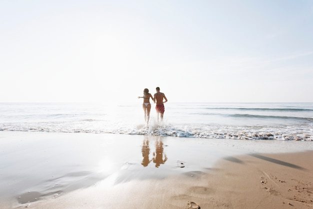 Cheerful couple running at the shore Free Photo