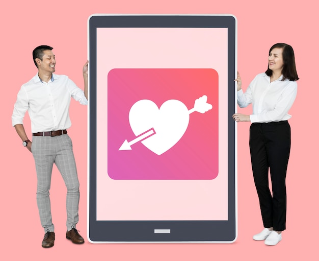 Cheerful couple showing online dating on a tablet Free Photo
