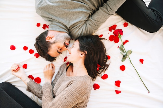 Cheerful couple touching noses on rose petals Free Photo
