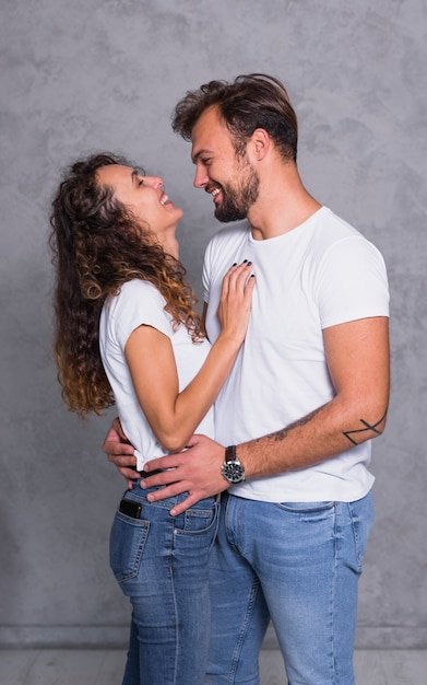 Cheerful couple in white hugging Free Photo