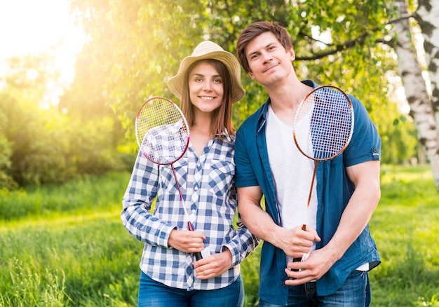 Cheerful couple with badminton rackets in park Free Photo
