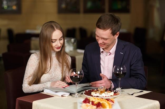 Веселая пара с меню в ресторане. Premium Фотографии