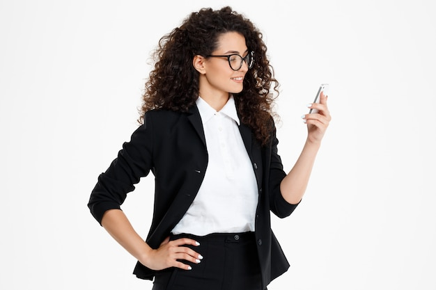 Cheerful curly business girl wearing glasses looking at phone Free Photo