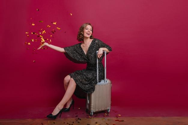 다가오는 여행을 위해 가방을 포장 한 후 쉬고 복고풍 검은 드레스에 쾌활한 곱슬 소녀 무료 사진