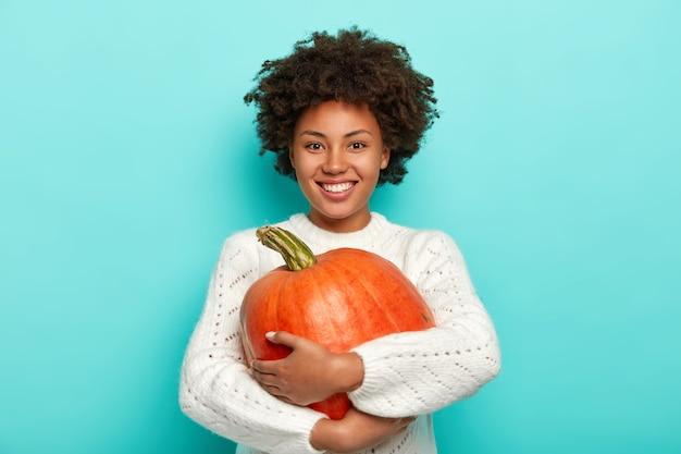 Веселая кудрявая женщина в белом свитере обнимает спелую тыкву, приятно улыбается Бесплатные Фотографии