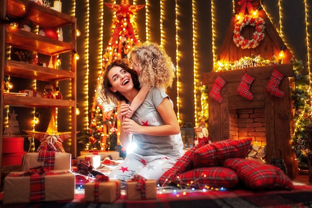 Cheerful cute curly little girl and her older sister exchanging gifts. Premium Photo