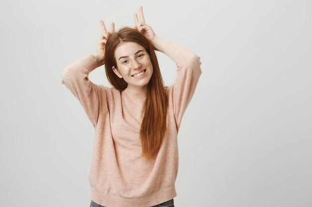 陽気なかわいい赤毛の女の子の頭の上に角を表示し、笑顔 無料写真