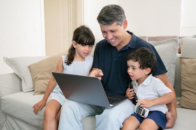 Веселый папа показывает содержимое ноутбука двум любопытным детям. семья смотрит фильм дома. Бесплатные Фотографии