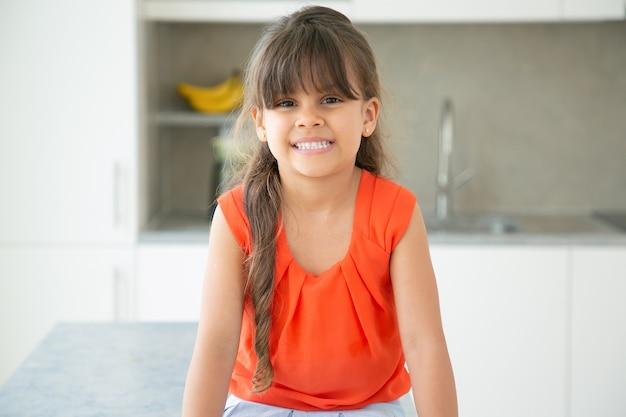 Веселая темноволосая латинская маленькая девочка в красной рубашке без рукавов позирует на кухне Бесплатные Фотографии