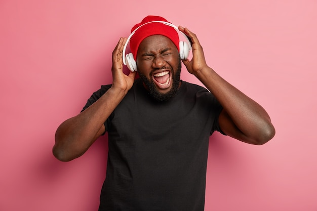Cheerful dark skinned hipster man uses headphones for noise cancellation, listens rock music, sings song aloud, wears red hat and black t shirt. Free Photo
