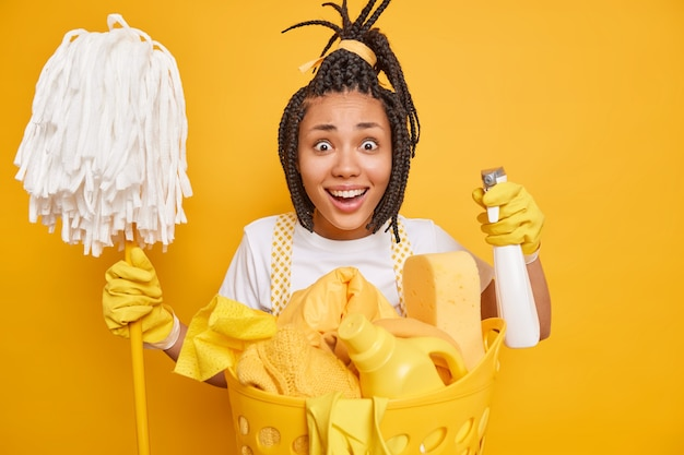 Cheerful dark skinned housewife holds chemical detergent and mop looks gladfully Free Photo