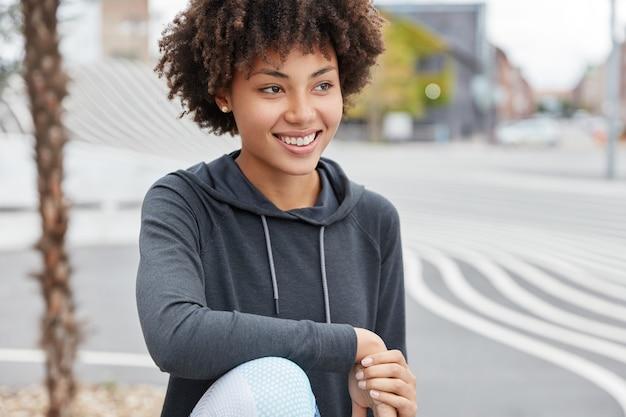 カジュアルな服を着て、魅力的な笑顔で陽気な暗い肌のティーンエイジャーは、暇な時間を楽しんでいます 無料写真