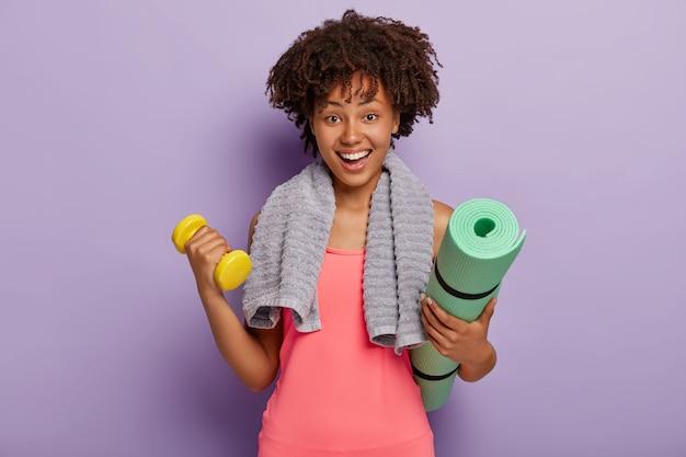Веселая темнокожая молодая афро-женщина держит циновку и гантели, тренирует мышцы в тренажерном зале, имеет счастливое выражение лица, полотенце на шее, носит розовый топ, модели в помещении у фиолетовой стены Бесплатные Фотографии