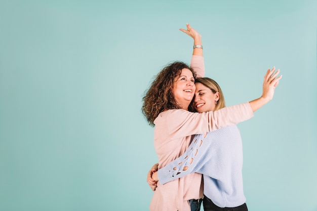 Cheerful daughter hugging mother Free Photo