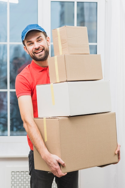Cheerful delivery man with parcels Free Photo