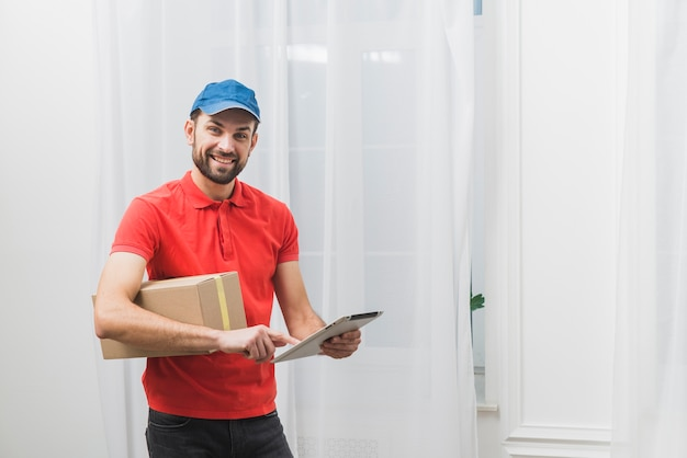 Cheerful delivery man with tablet and box Free Photo