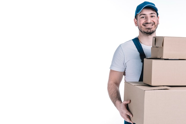 Cheerful deliveryman carrying stack of parcels Free Photo