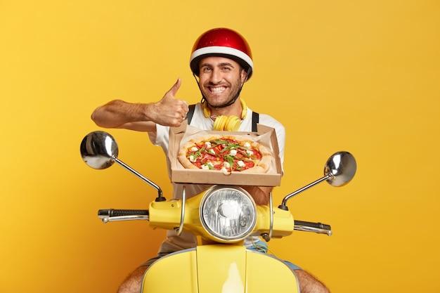 Веселый курьер в шлеме за рулем желтого скутера, держа коробку для пиццы Бесплатные Фотографии