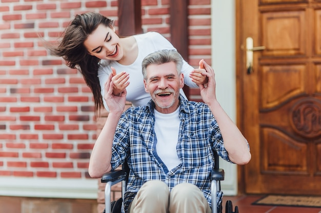 Cheerful disabled grandfather in wheelchair welcoming his happy granddaughter  near nursing home Premium Photo