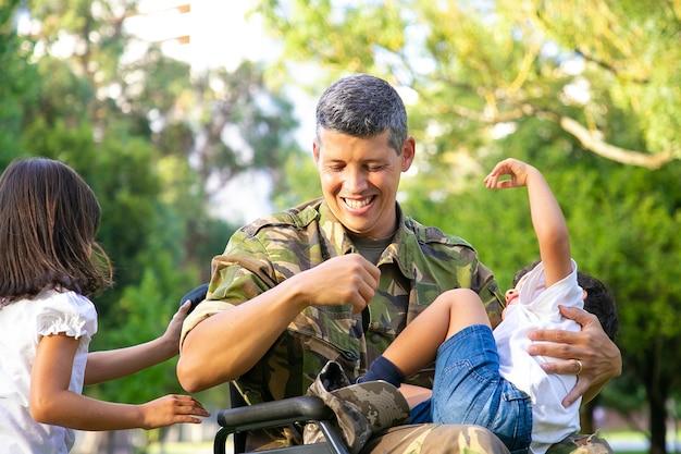 公園で2人の子供と余暇を楽しんでいる陽気な障害のある軍のお父さん。車椅子のハンドルを握っている女の子、お父さんの膝の上で休んでいる男の子。戦争または障害の概念のベテラン 無料写真