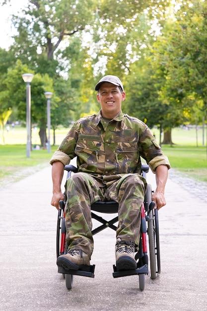 迷彩服を着て、都市公園の歩道を移動している車椅子の陽気な障害のある軍人。正面図。戦争または障害の概念のベテラン 無料写真