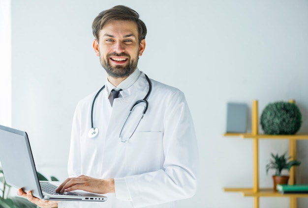 Cheerful doctor with laptop looking at camera Free Photo