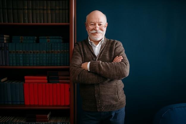 メガネで陽気な老人は、ホームオフィスの本棚でポーズします。ひげを生やした成熟したシニアポーズリビングルーム、老年実業家 Premium写真